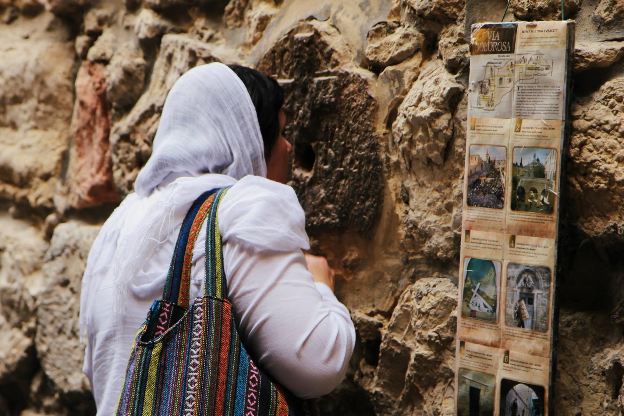 Vrouw kust de muur bij de Via Dolorosa