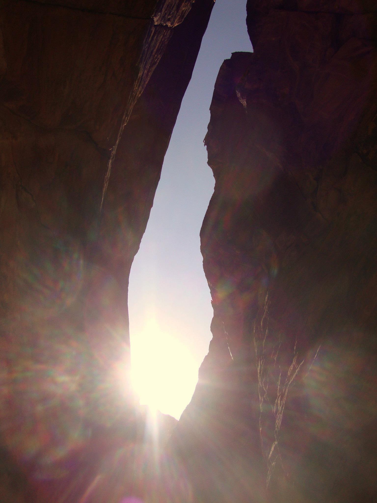 De zon breekt door tussen de rotsen