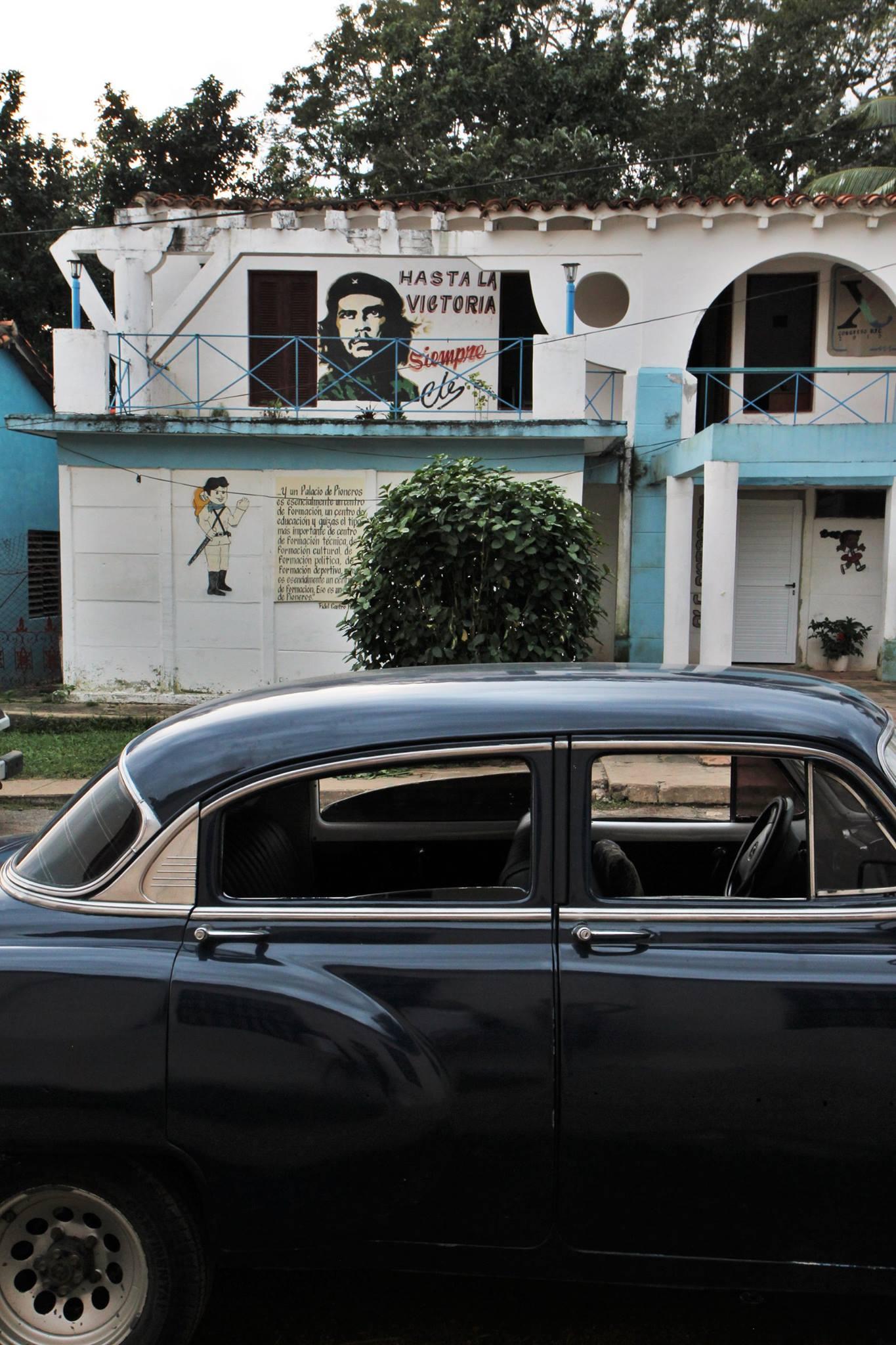 Een oude Amerikaanse auto naast een muurschildering van Che in Viñales.